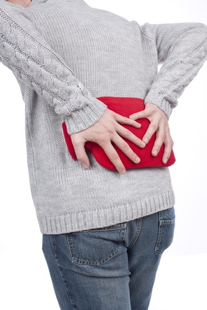 intervertebral disc: man with hot bottle and back pain Stock Photo