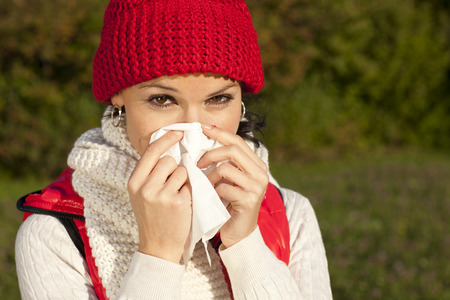 immune system: Young woman with handkerchief in natural surroundings Stock Photo
