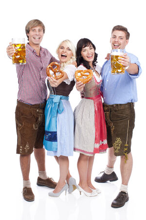 traditional costume: Four young people in traditional costume  with beer glasses
