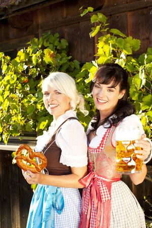 prost: young woman couple in traditional costume  with beer glasses Stock Photo