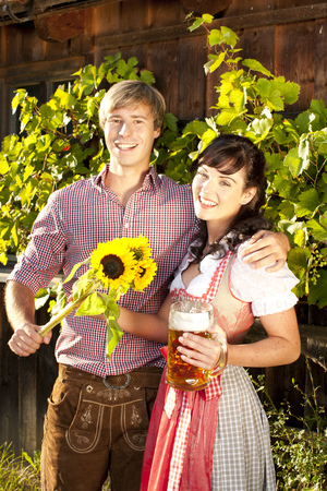 traditional costume: young couple in traditional costume  with beer glasses