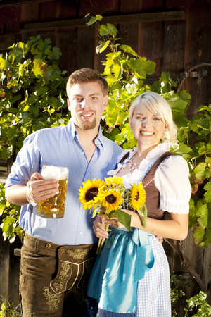 prost: young couple in traditional costume  with beer glasses