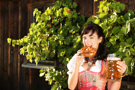 prost: Young bavarian woman with beer and pretzel