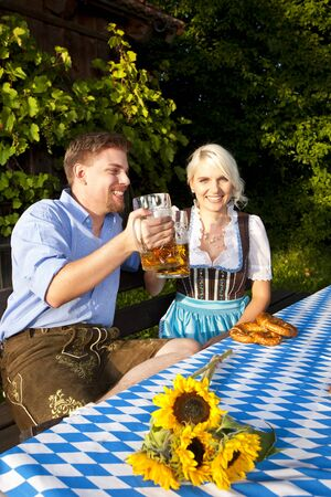 prost: Young bavarian couple outdoor with beer and pretzel Stock Photo
