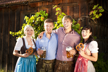 Four young bavarian people in front of a typical hut photo