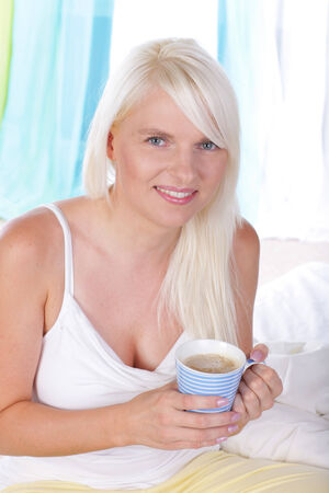 Smiling Woman drinking coffee in her bed Reklamní fotografie