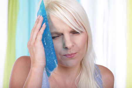 cheek: Woman holds an  ice pack on her cheek