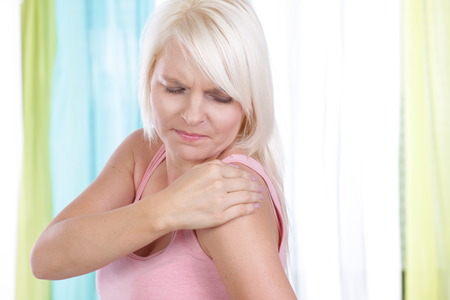 calcification: Young woman holds her shoulder