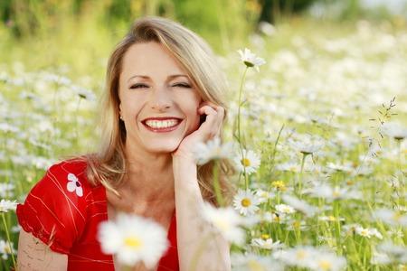 Happy woman in flower field Stockfoto