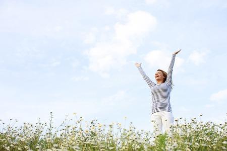 花畑に伸ばされた腕を持つ幸せな女 写真素材