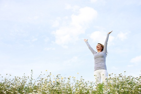 Happy woman with stretched arms in flower field