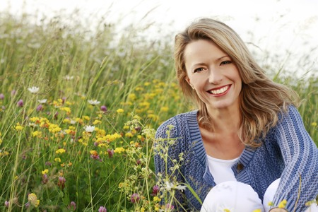 femme chatain: Bonne femme d'�ge moyen dans le champ de fleurs sauvages