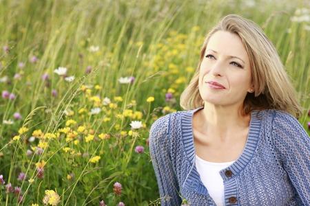 vrouw blond: Gelukkige vrouw van middelbare leeftijd in wilde bloem veld