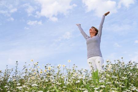 Happy woman in marguerite flower field
