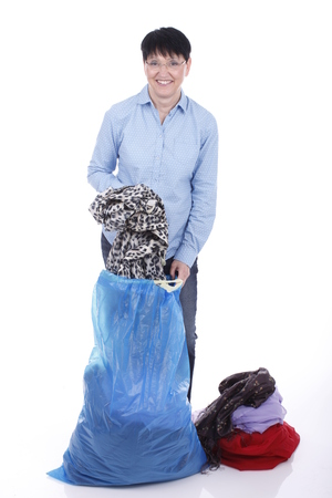 used clothes: Elderly woman puts used clothes in a big bag isolated on white