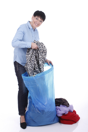 discard: Elderly woman puts used clothes in a big bag isolated on white