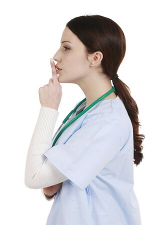 medical assistant: Young medical assistant from the side with finger on her lips