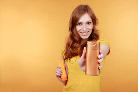 red haired woman: Young  red haired woman with sun lotion