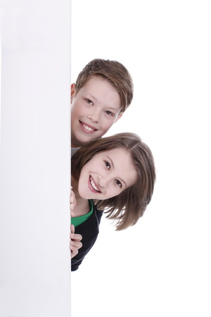 looking in corner: Boy and girl are looking round the corner of an empty board