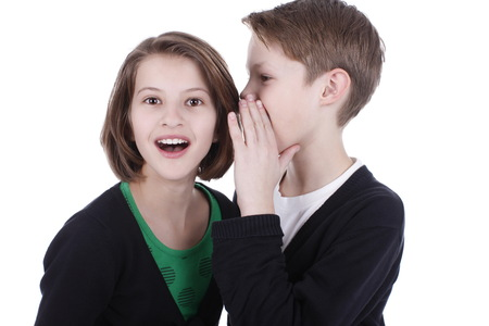 narrate: Boy whispers secrets in the girls ear isolated Stock Photo