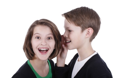 Boy whispers secrets in the girls ear isolated Stock Photo