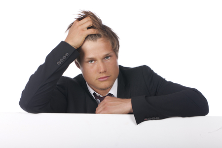 frazzled: Exhausted young businessman leaning across a empty board isolated