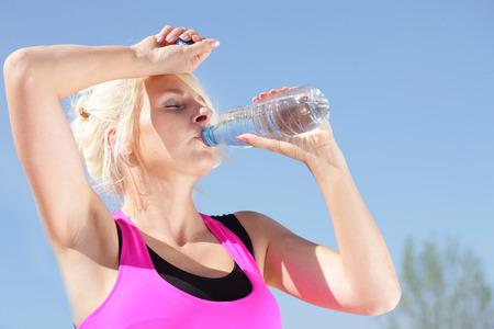 estado del tiempo: Mujer de agua potable en el clima caliente