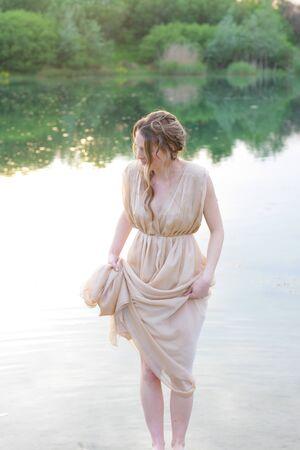 traje de gala: Hermosa mujer con vestido de noche de pie en un lago