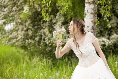 vestido blanco: Mujer feliz en el vestido blanco est� soplando las semillas de diente de le�n