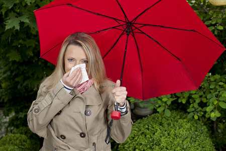 running nose: Woman with handkerchief and umbrella outdoor has caught a cold Stock Photo