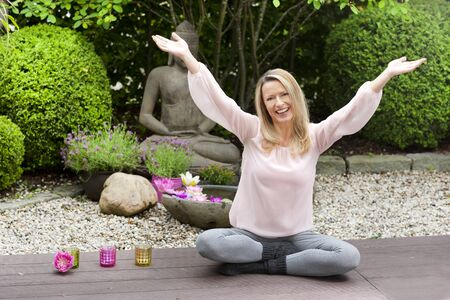 Blond happy middle aged woman with arms outstretched in zen garden Reklamní fotografie