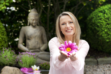 Happy middle aged woman offers flowers in zen garden smiling Imagens