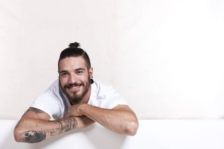 white wall: Friendly young tattoo man with pony tail leaning across a white wall Stock Photo