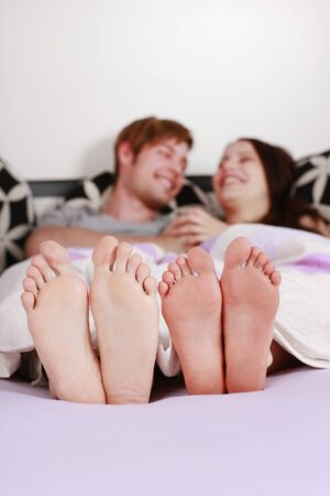 bed feet: Happy young couple lying in bed