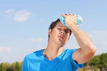 Young man with icepack on his foreheat in the summer heat Stockfoto