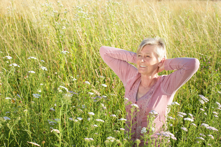 Happy senior woman active in nature in summer