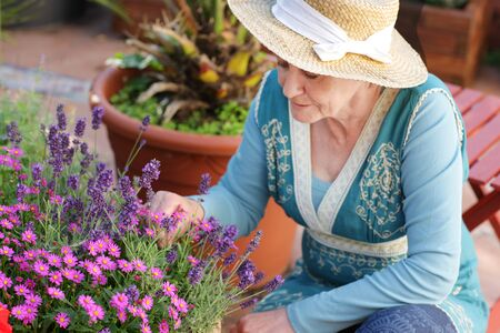Happy senior woman with flowers  on her terrace