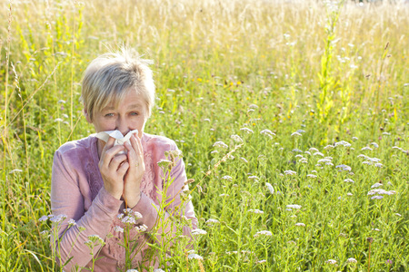 Senior woman with handkerchief in the grass outdoor
