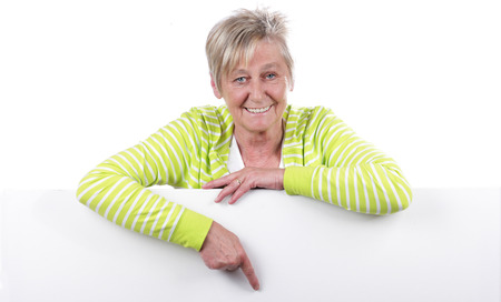 woman behind: Happy older woman behind a white board isolated on white
