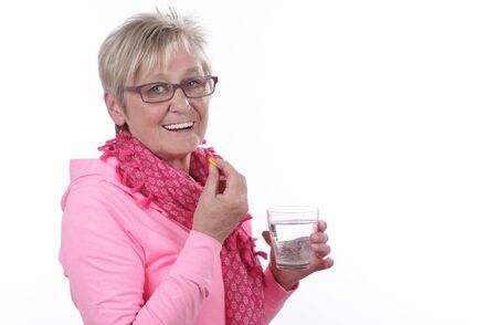 ingestion: Older woman is taking a tablet isolated Stock Photo