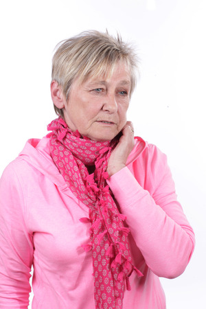 sore throat: Older woman with scarf and sore throat isolated Stock Photo