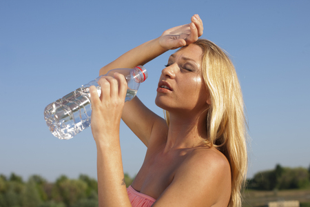 hot drinks: Young woman drinking water in hot summer outdoor Stock Photo