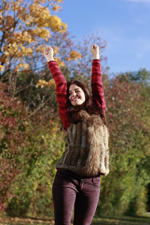 raised arms: Attractive woman with raised arms in autumn