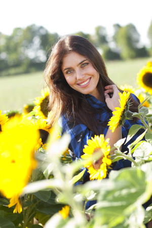dark haired woman: Happy dark haired woman with sun flowers smiling Stock Photo
