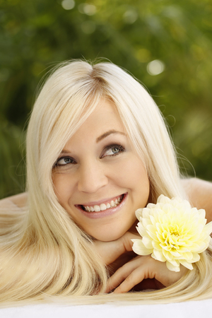 big flower: Happy woman with big flower looking up and smiling Stock Photo