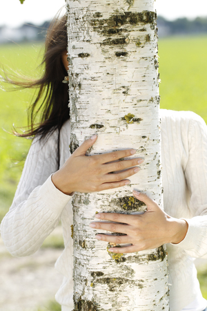 anonymus: Young attractive woman close to a birch tree outdoor in autumn Stock Photo