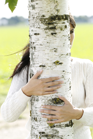 Young attractive woman close to a birch tree outdoor in autumn Stock Photo