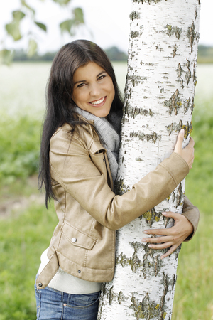 birch tree: Woman outdoor embraces a birch tree in autumn Stock Photo