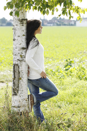 birch tree: Young attractive woman close to a birch tree outdoor in autumn Stock Photo