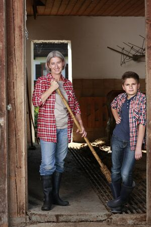 doorframe: Older woman and boy leaning in the doorframe of a stable on a farm Stock Photo